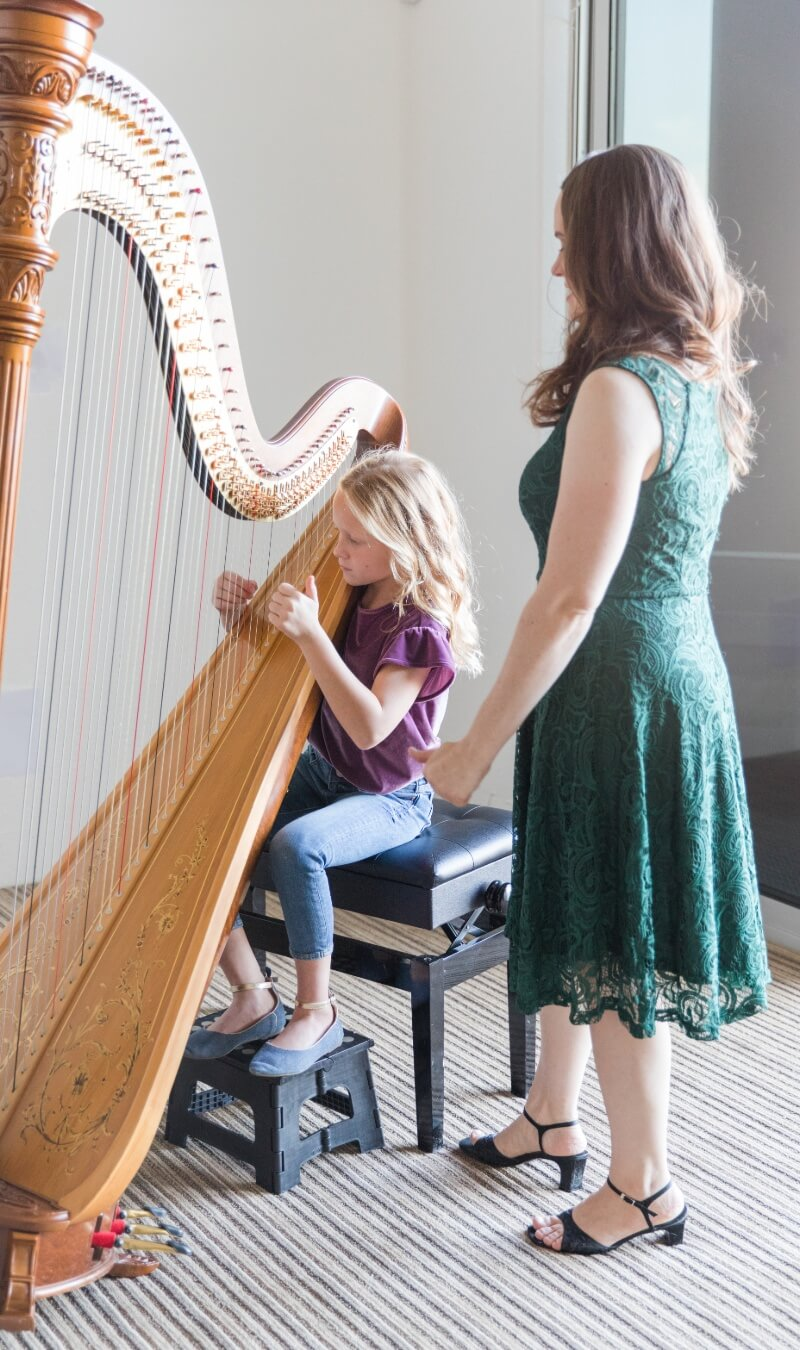 Harp lesson with teacher wearing a green dress